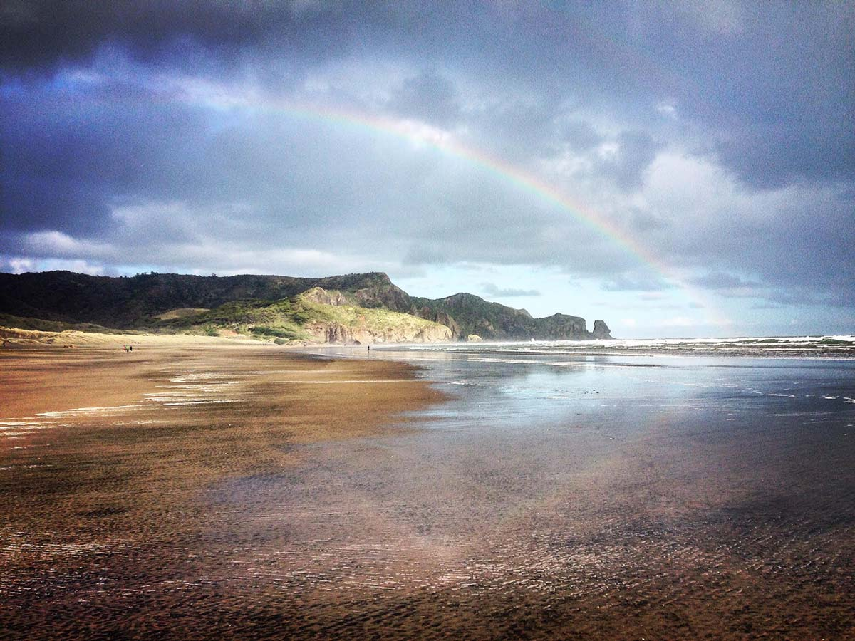A beach in New Zealand with a rainbow shining over it