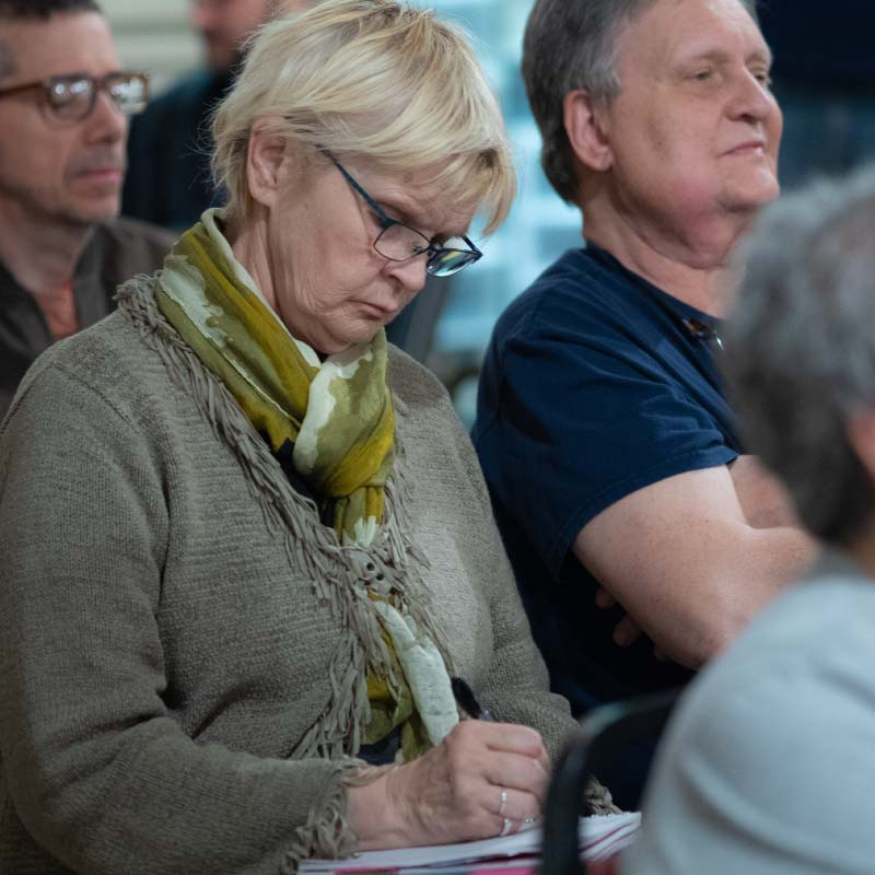 Woman taking notes at a community meeting